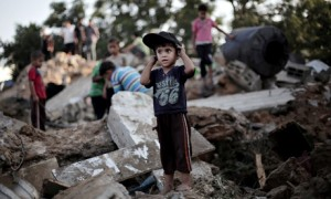A Palestinian boy plays in the rubble of a home wrecked in an Israeli air raid on Beit Hanoun, Gaza