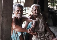 Sushil Kumar Mondol, left, sits inside his home in a coastal area of southern Bangladesh. (Photo by Stephan Uttom)